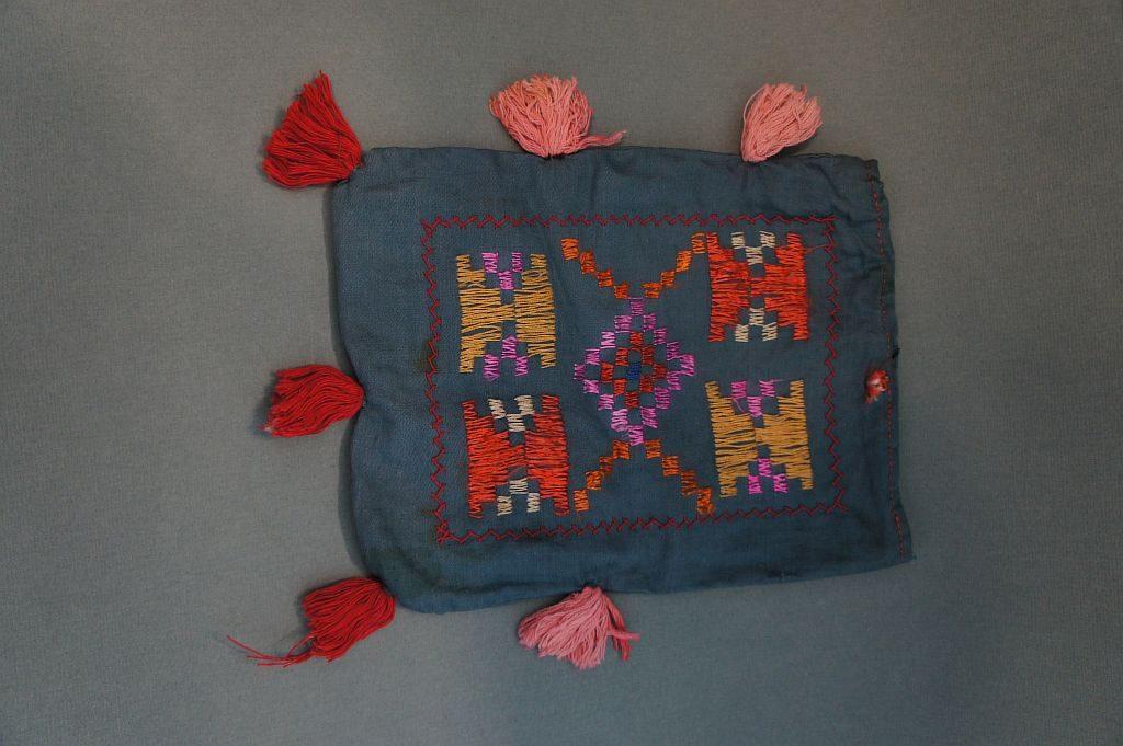 Кисет «Янсык», вышитый разноцветными нитями прямоугольной формы. Это небольшой мешочек для хранения вещей, затягиваемый шнурком. Часто в кисете хранят табак. Имеется вышивка в виде башкирского орнамента.
