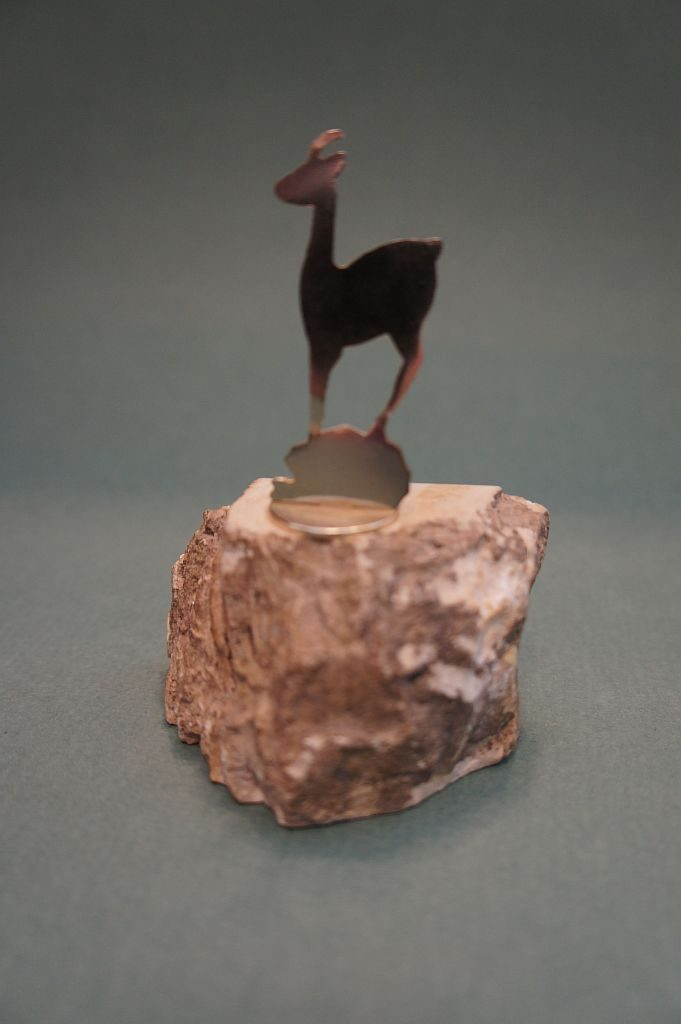 Сувенир в виде антилопы, стоящей на камне. Фигура антилопы и камня сделаны из металла.Привезен из курортного горда Карловы Вары в Чехии. Основание сувенира из камня. Принадлежал народному писателю Башкортостана Ахияру Хакимову.
