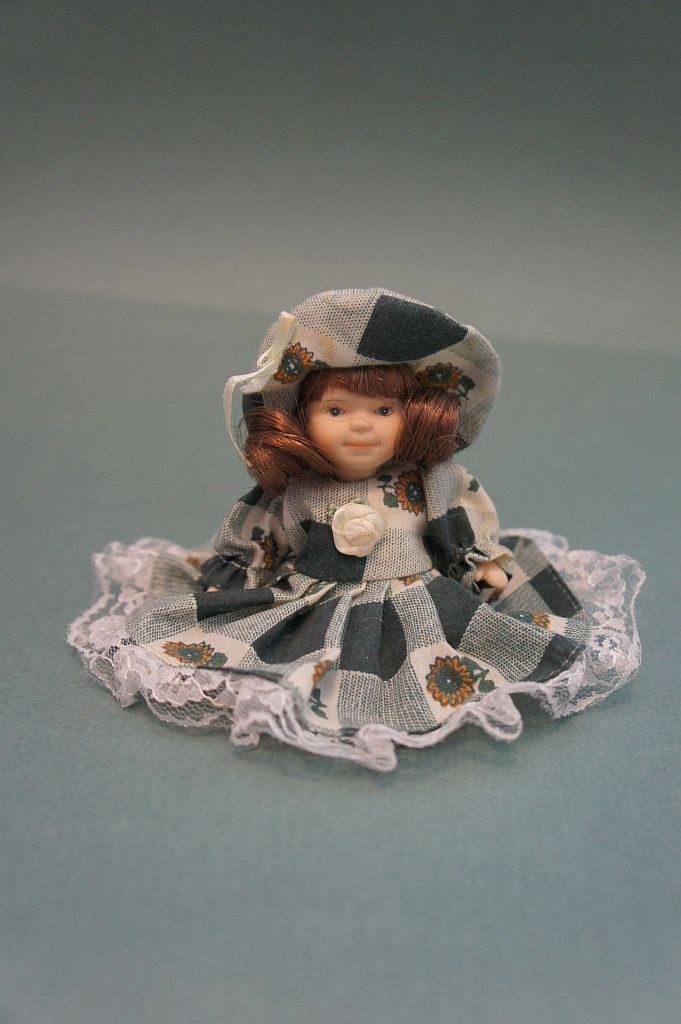Сувенирная кукла ручной работы в женском платье и шляпе. Находится в положении сидя на коленях.